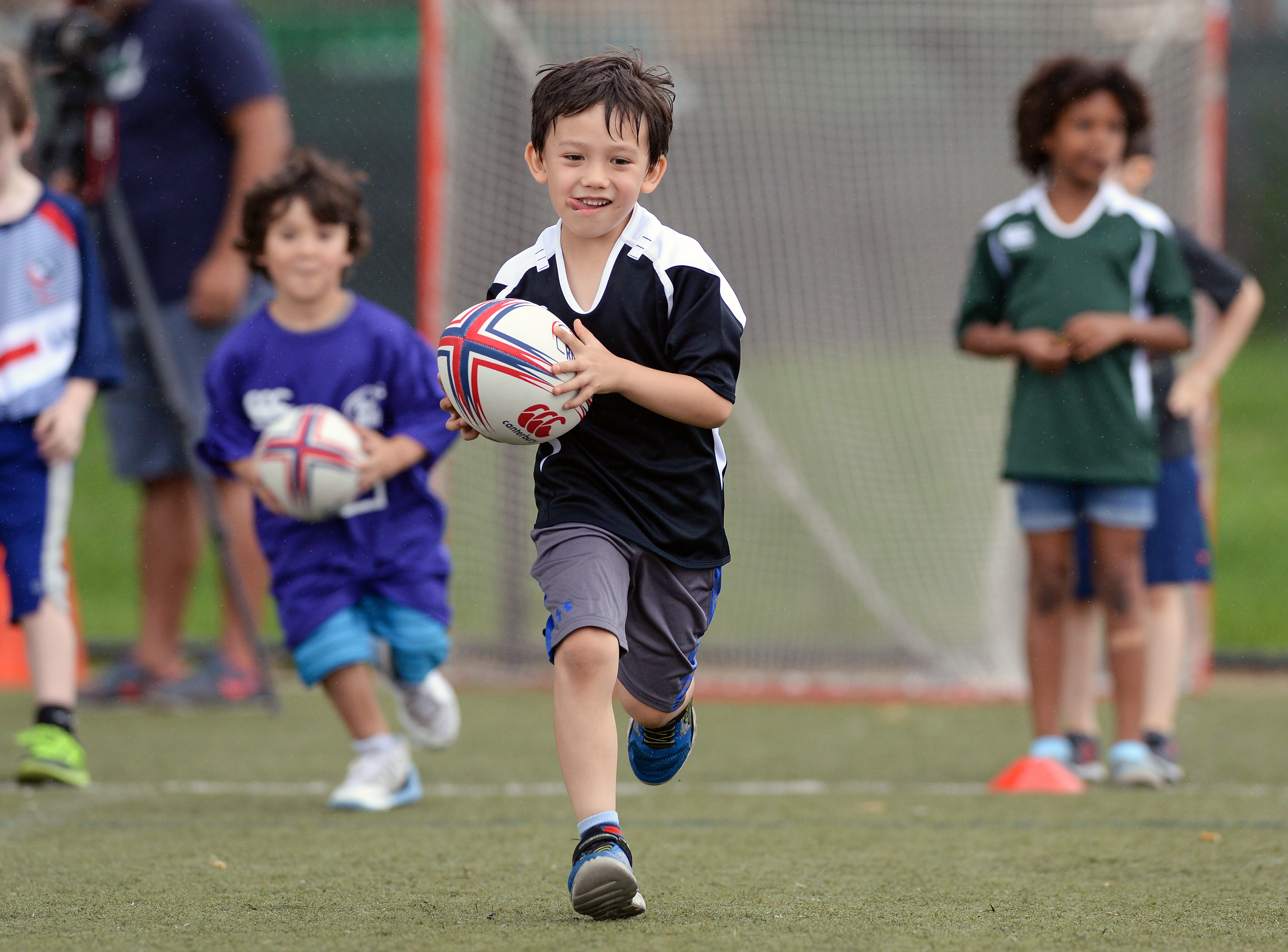 Smiling Child playing Rugby on the field